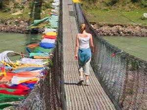 Frau auf Hängebrücke mit bunten Fahnen in Bhutan