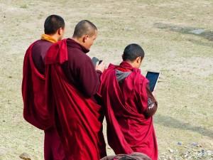Drei Mönche mit Smartphone und Tablet PC