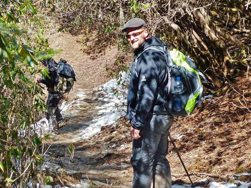 Wanderer auf einem Waldweg mit Schneeresten in Bhutan