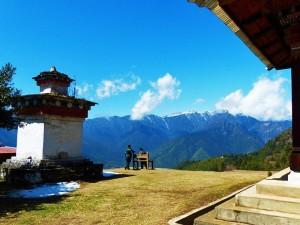 Wanderer an einem buddhistischen Tempel in Bhutan mit Ausblick auf die schneebedeckten Berge