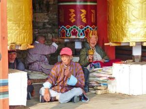 Ältere Bhutaner im Gebet vor den Gebetsmühlen in Thimphu.