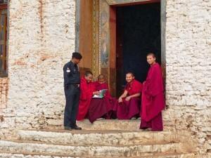 Lachende Mönche sitzen am Eingang des Trashigang Dzongs
