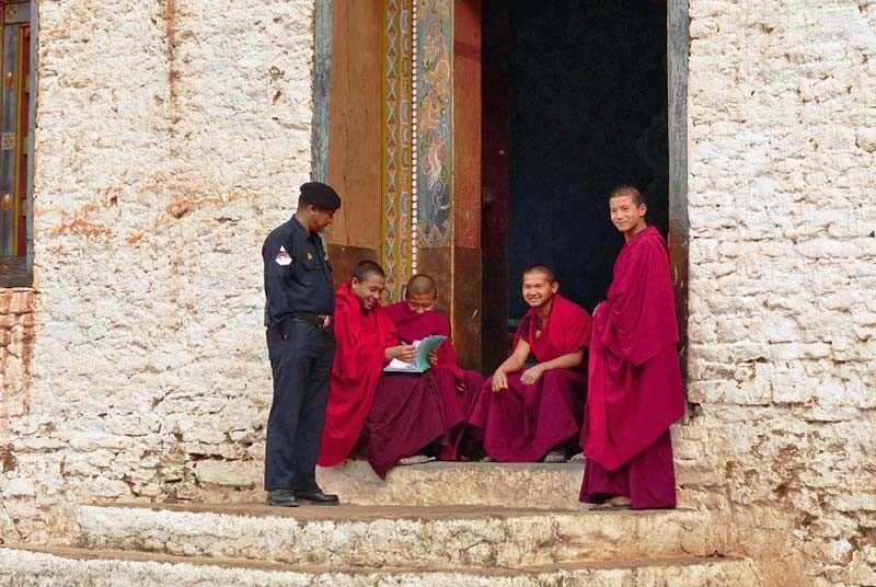 Lachende Mönche sitzen am Eingang des Trashigang Dzongs.