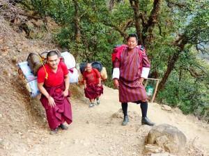 Mönche mit schwerem Gepäck auf dem Weg zum Cheri Kloster bei Thimphu