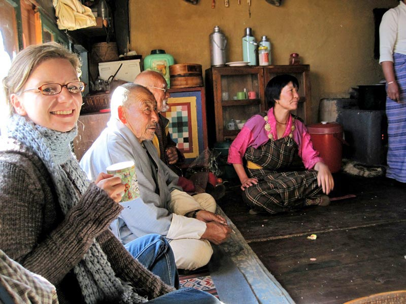 Touristin und Bhutanesen im Homestay in Tshaluna bei Thimphu.