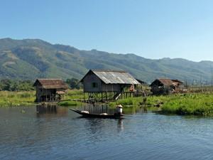 Lontailboot und Pfahlhäuser am Inle See in Myanmar