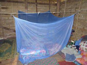 Ein einfaches Bett mit Mückennetz