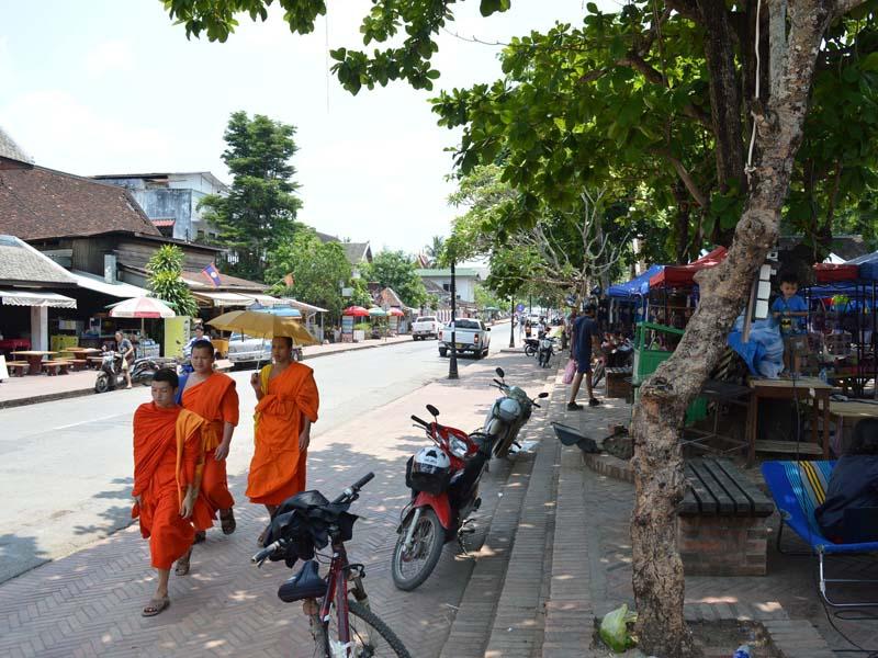 Mönche laufen eine Straße entlang