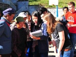 Helferin erklärt Einheimischen den Ablauf der Kleiderverteilung