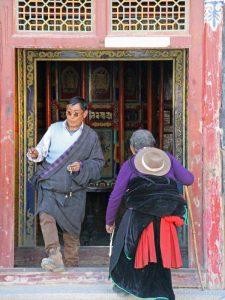 Tibetische Pilger vor einem Gebetsmühlenpfad