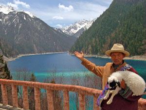 ein Tibeter mit Lamm vor einem malerischen See