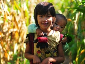 Kind trägt Baby auf dem Rücken