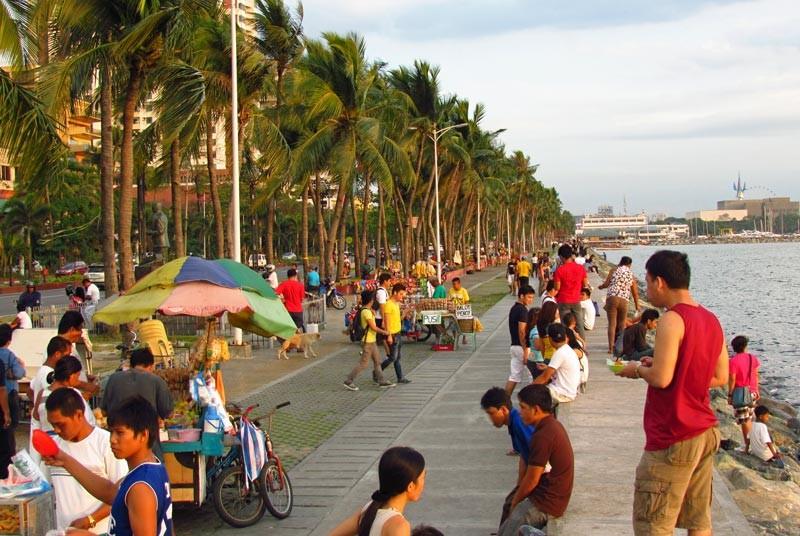 Menschen auf der Promenade von Manila bei Sonnenuntergang