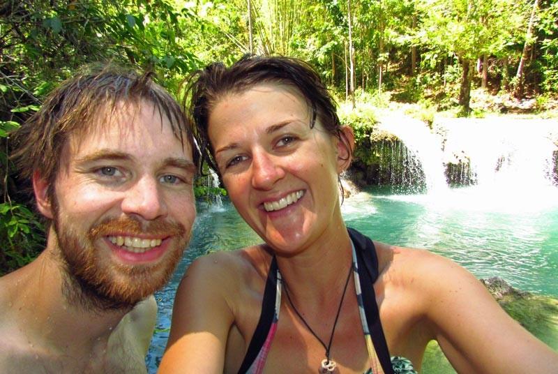 Paar vor türkisblauem Wasserfall auf Siquijor