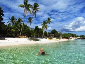 Frau im Meer vor Palmen