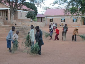 Kinder fegen mit Laubbesen einen großen sandigen Platz