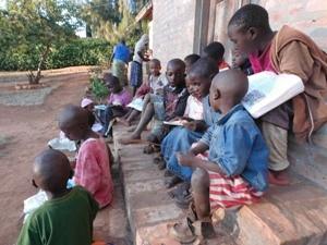 Kinder sitzen auf Stufen vorm Haus und lesen