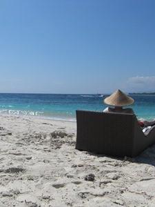 Reisender auf einer Liege am Strand von Gili Meno