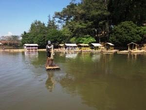 Einheimischer Fischer auf einem langen Bambusfloß.