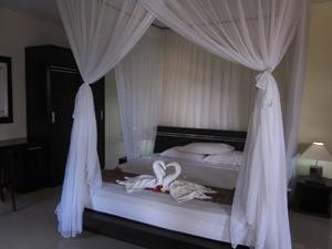 Bett mit Moskitonetz in einem Hotel auf Java