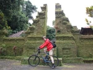 Mann auf Fahrrad vor Tempelanlage