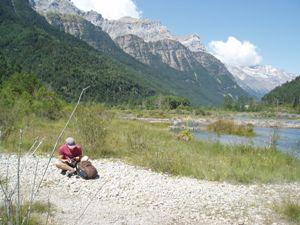 Mann sitzt und liest am Seeufer vor Bergkulisse