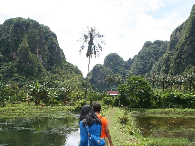 Reisende wandern zwischen den Karstfelsen auf Sulawesi.
