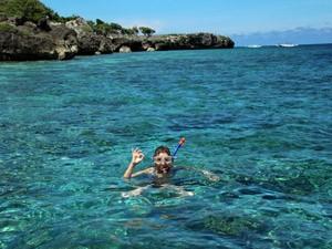 Taucherin im azurblauen Wasser in Bira auf Sulawesi.
