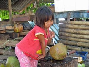 Ein Mädchen trinkt frische Kokusnussmilch.
