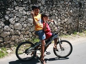 Kinder auf dem Fahrrad am Wegesrand - Bali Flitterwochen