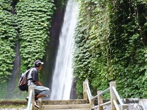 Reisender genießt Ausblick auf Wasserfall in Munduk