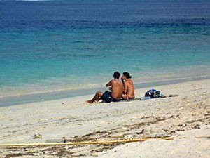 Paar sitzt am Strand auf Gili Meno