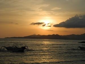 Die untergehende Sonne über dem Meer bei Candidasa auf Bali - Bali Flitterwochen