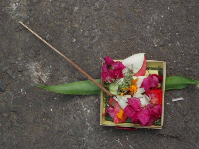 Blumige Opfergaben auf einer Straße auf Bali.