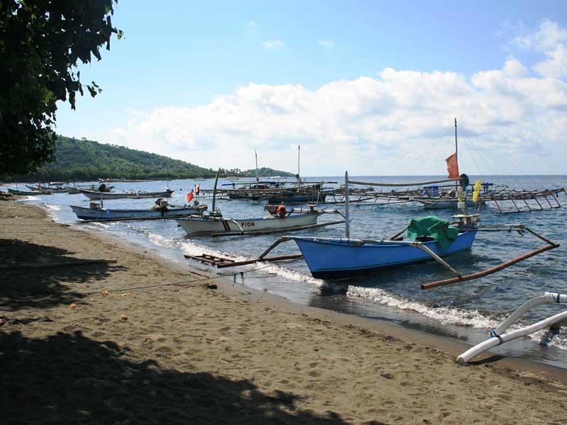 Boote ankern am Lavastrand von Pemuteran