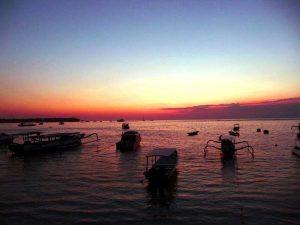 Die untergehende Sonne färbt das Meer vor Jimbaran blutrot - Bali Flitterwochen