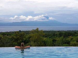 Reisende schaut von einem Pool aus auf dem Gunung Agung.