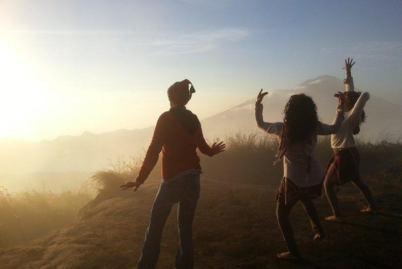 Reisende begrüßen die Sonne am Gipfel des Batur Vulkans.