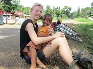 Tansanisches Kind auf dem Schoß einer Touristin am Wegesrand