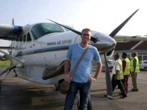 Reisender vor einer kleinen Propellermaschine