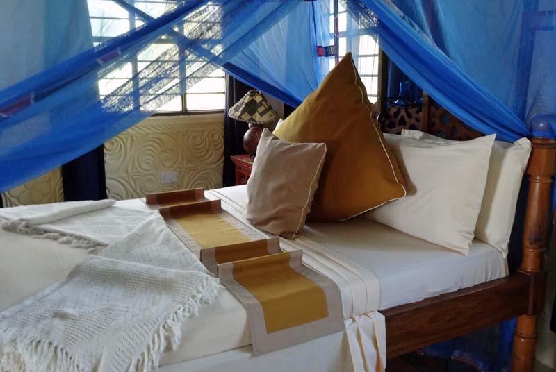 Ordentliches Bett im großzügigen Zimmer auf Sansibar