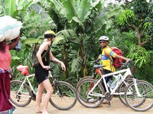 Guide und Touristin mit den Mountainbikes unter Bananenplantagen