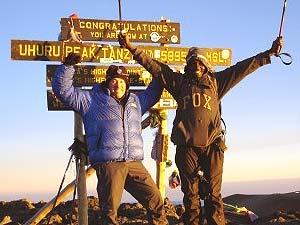 Reisende am Gipfel des Kilimanjaro nach erfolgreichem Aufstieg
