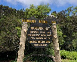 Informationstafel der Mandara Hütten vor grünem Wald