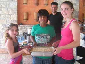 """Olympisch koken met boer Dimitris """"Omdat Nelson de kok van onze familie is, mag hij beginnen met het snijden van de paprika's en dat doet hij super, met de juiste techniek. Daarna worden ook Chelsea en Kaylee in het voorbereidings- en kookproces opgenomen en al snel hebben ze alle drie wisselende taken, onder leiding van de twee koks. Wanneer de pastitsio in de oven staat gaan ze verder met de Griekse salade en als die in de koelkast staat, mag Kaylee het recept opschrijven. Het smaakt allemaal heerlijk. We praten nog wat na met Nikos, over Griekenland en Nederland voordat hij van zijn vrije middag gaat genieten en wij gaan zwemmen, nog nagenietend van deze cursus: zoveel leuker dan in een overvolle schnitzelbus van attractie (even rondkijken en snel weer weg) naar shopping stop (kijken, maar vooral kopen) te worden gereden en uiteindelijk weinig tot niets gezien en gedaan te hebben..."""" (reisverslag Familie Westerhoff)"""