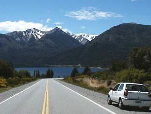 Straße mit See und Bergen im Hintergrund