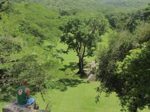 Mann blickt von Hügel auf alte Tempelanlage herunter