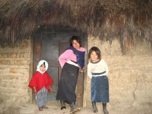 Drei Kinder vor einer Dorfhütte