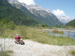 Mann sitzt vor Bergkulisse an einem See und liest
