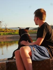 Junge sitzt mit Hund im Boot